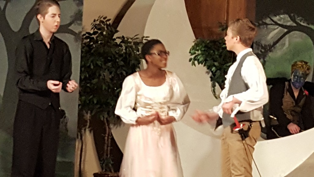 Demetrius, Helena, and Lysander in the middle of a dramatic scene.