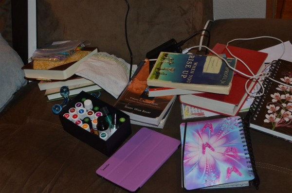 A stack of school books, essential oils, a Kindle and some journals.