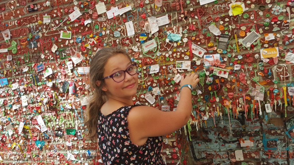 Sarah adds her gum to the wall.